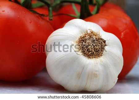 Close up to Garlic together with tomato on kitchen counter