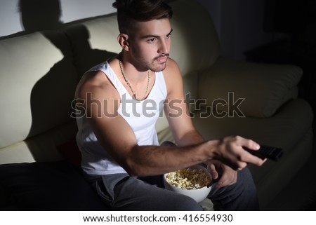 Close up to handsome young man watching movies and eating popcorn. Indoor. - stock photo