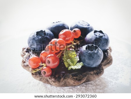 Close up to mini tart stuffed with chocolate pudding and berry fruits,selective focus  - stock photo