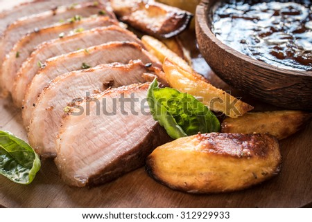 Close up to served pub meal, pork fillets,baked potatoes and homemade bbq sauce