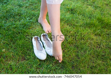 close-up to the feet of a balerina dancing on the grass