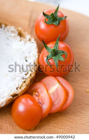 close up tomatoes cherry and piece of bread with cottage chees - stock photo