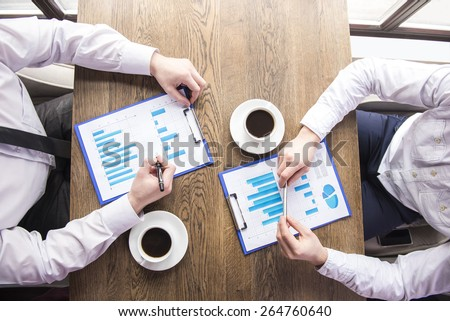 Close-up. Top view. Businessman analyzing graphs with cup of coffee in restaurant. - stock photo