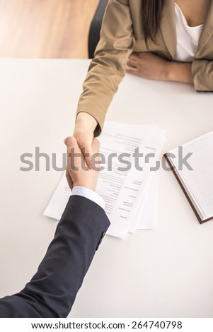 Close-up. Top view. Male candidate shaking hands with businesswoman at desk in office - stock photo