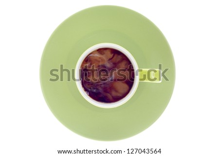 Close-up top view of a green coffee cup and saucer over white background. - stock photo