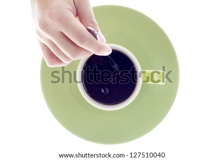Close-up top view of a person stirring coffee over white background. - stock photo