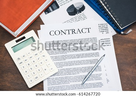 Close-up top view of contract, calculator, business charts and notebooks on wooden table