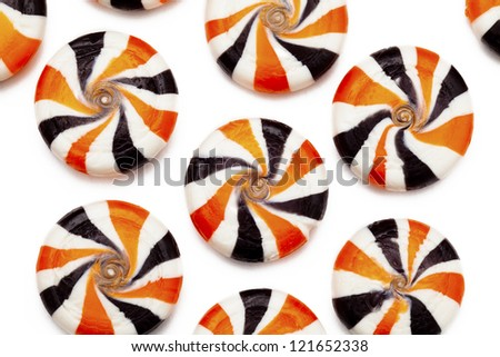 Close-up top view of multi colored hard candies placed side by side over white background. - stock photo