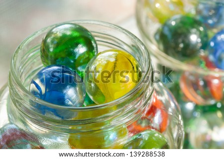 Close up top view of one inch Cat's Eye Shooter Marbles in glass mason jars - stock photo