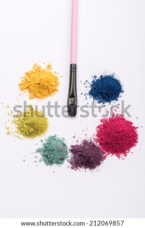 Close-up top view of professional make-up brush surrounded by heaps crashed in small pieces eye shadow in pink, blue, yellow, green and purple colours isolated on white background