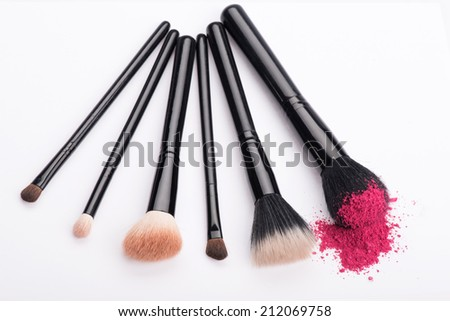Close-up top view of set of professional make-up brushes with natural  bristle and black ferrule in different sizes, one with crashed pink eye shadow isolated on white background - stock photo