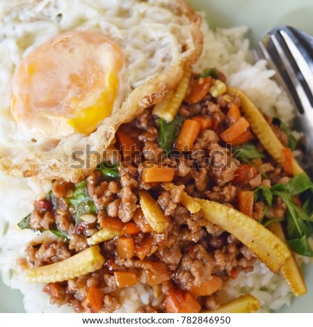 Close up top view of stir fried red chilli paste with minced pork, carrot and young corn topping with fried egg on hot rice (Cooked to order)