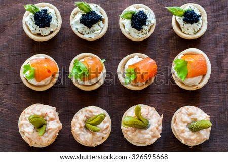 Close up Top view of variety of multiple mini puff pastry tart lets on wooden table. Open pastries filled with seafood.
