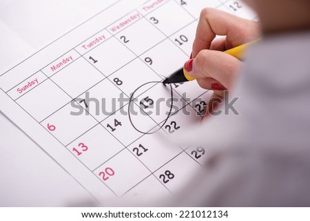 Close-up top-view photo of calendar with a datum circled by young woman with red nails with a back marker, concept of time management at work - stock photo