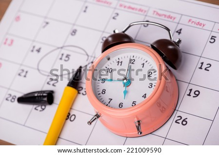 Close-up top-view photo of calendar with a datum circled with a black marker lying on it, with selective focus on an alarm clock, concept of time management at work - stock photo