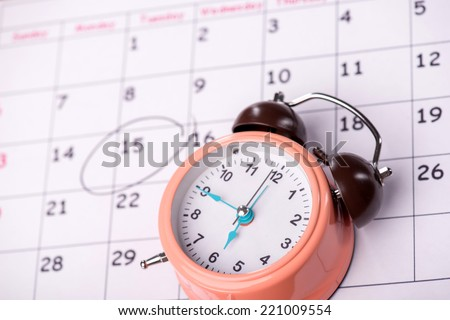 Close-up top-view photo of calendar with a datum circled with a black marker, with selective focus on an alarm clock, concept of time management at work - stock photo