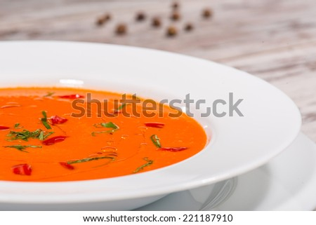 Close-up top-view picture of cold tasty tomato soup gazpacho with species on the wooden table in vegan caffee with copy place - stock photo