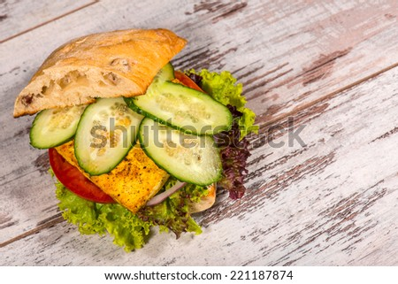 Close-up top-view picture of tasty vegetarian sandwich with tofu, tomatoes, salad and cucumber on the white plate standing on the wooden table in vegan caffee, with copy place - stock photo