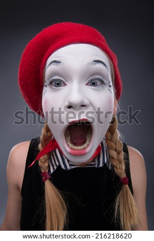 Close-up top-view portrait of funny female mime in red head and with white face yawning at looking at the camera isolated on grey background with copy place - stock photo