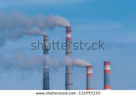 Close-up tops of smoking pipes of power plant on blue sky background, horizontal photo, - stock photo