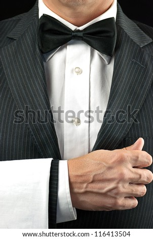 Close-up torso shot of a fine dining waiter in a bowtie and tux with a white pressed napkin over his arm.