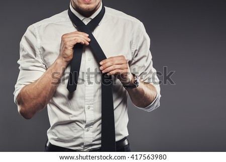 Close up torso view of a businessman wearing a white shirt dressing tying his necktie on grey with copy space - stock photo
