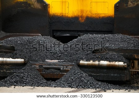 Close-up tracked paver at asphalt pavement works for road under construction. - stock photo