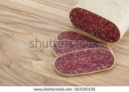 Close-up traditional sliced meat sausage salami on wooden board. All in focus. - stock photo