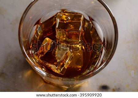 Close-up tumbler with scotch. Beautiful ice cubes in whisky. Real beverage for real men.