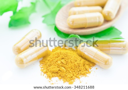 Close up turmeric herbal capsules with green leaf on white background. - stock photo