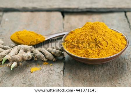 Close up Turmeric powder in bowl on wooden background.