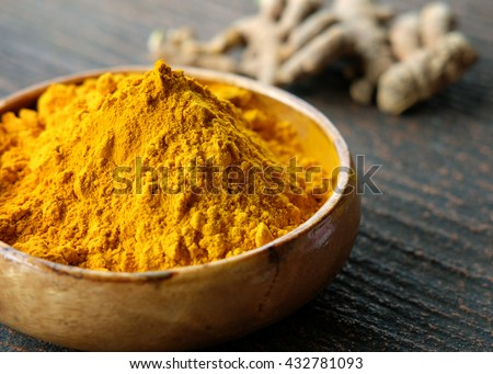 Close up Turmeric powder in wooden bowl.