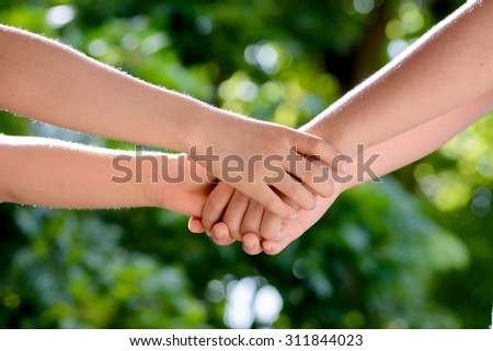 Close up two boy hands hold together on green bokeh background from tree leaf