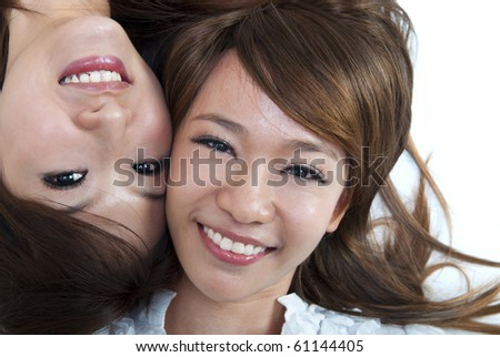 Close up two cute girls lying on floor - stock photo