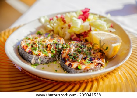 close-up two grilled swordfish steaks with lemon slice and cabbage - stock photo