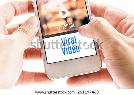Close up Two hand holding smart phone with Viral Video word and icons, Digital concept. - stock photo