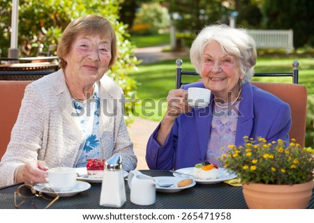Close up Two Happy Senior Women Looking at the Camera While Having Coffee Time at the Garden Table. - stock photo