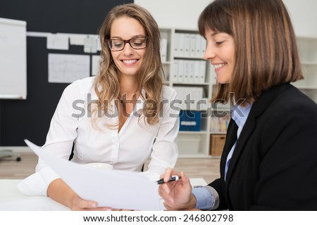 Close up Two Happy Young Businesswomen at the Office Talking About Business Report on Paper. - stock photo