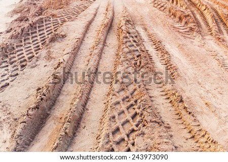 Close up tyre tracks on marshy road - stock photo