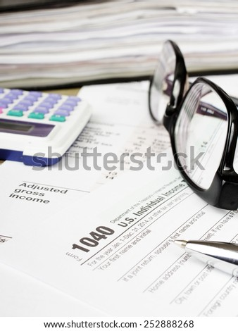 Close up U.S. Individual tax form 1040 with glasses, calculator and pen.