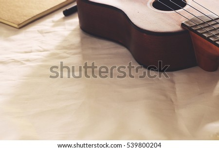 close-up ukulele on  vintage fabric in soft-focus in the background.  over light and warm fall colors