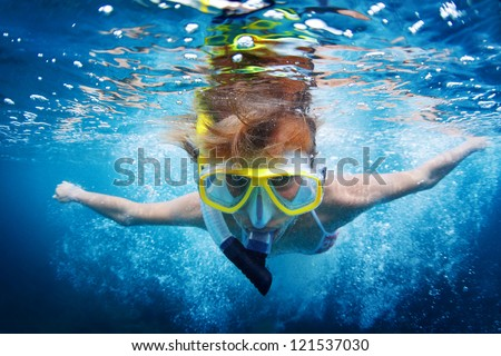 Close up underwater portrait of a woman in mask making bubbles in a sea with raised hands