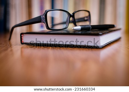 Close up Unisex Eyeglasses with Black Frame on Top of the Book at the Wooden Table at the Office. - stock photo