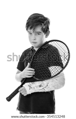 Close up upper body shot of a cute young boy who has broken his left arm and is unhappy because he can't play tennis - stock photo