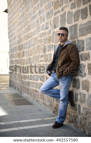 Close-up urban outdoor portrait of a handsome man with sunglasses against ancient wall, image toned and noise added.  - stock photo
