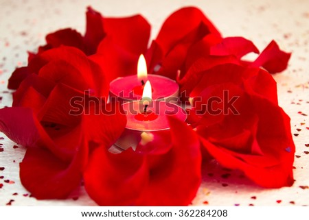 Close up Valentine candle light with rose petals - stock photo