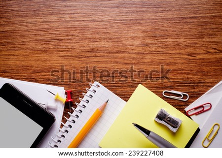 Close up Various Educational Supplies and Mobile Phone Gadget on Brown Wooden Table with Copy Space for Texts . - stock photo