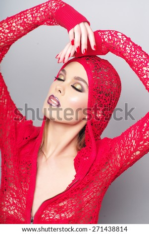 Close-up vertical portrait of beautiful woman wearing red clothes with make-up on the face with closed eyes  on grey background - stock photo