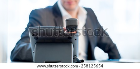 Close up view across the desk of the hands of a businessman making a  phone call as he sits at his desk in a communications concept. - stock photo