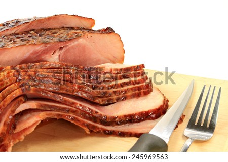 Close-up view Finally backed pre cooked smoked Spiral-cut of Pork Ham over wooden cutting board ready to arrange American South Traditional New Years Day meal over white background
